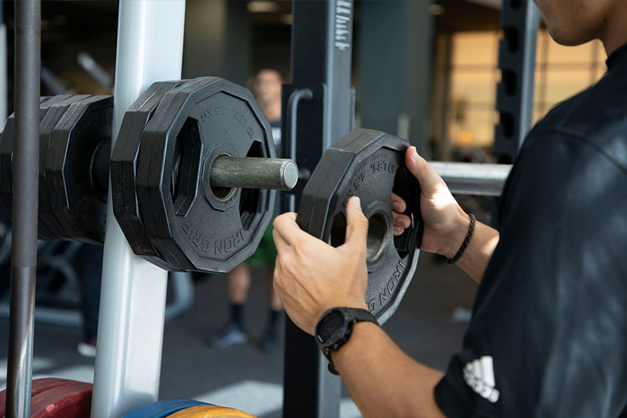 Hands putting weights on to a lifting machine for a workouut