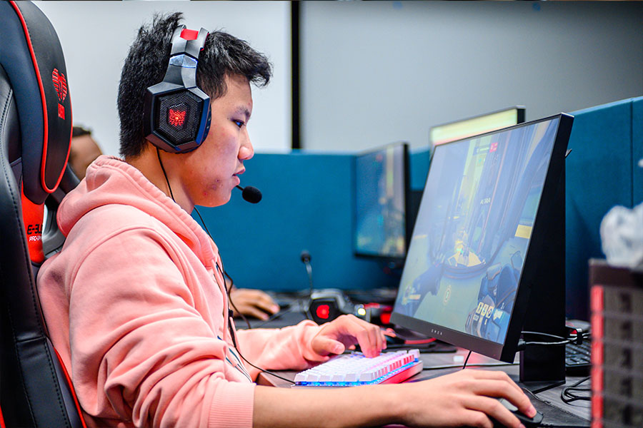 Male student playing video games at a computer with a headset on