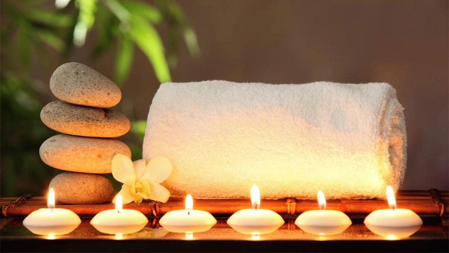 an image of relax in the rec spa with stones, towel and candels