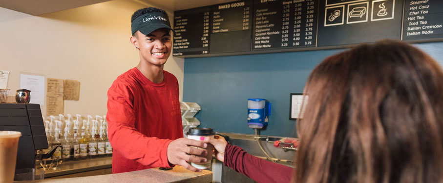 African American student in a red shirt serving coffee at the Lions Den to a female