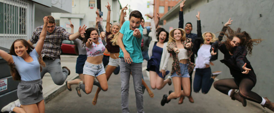 Students jumping in celebration in an alleyway pointing at the camera lmu del rey players banner