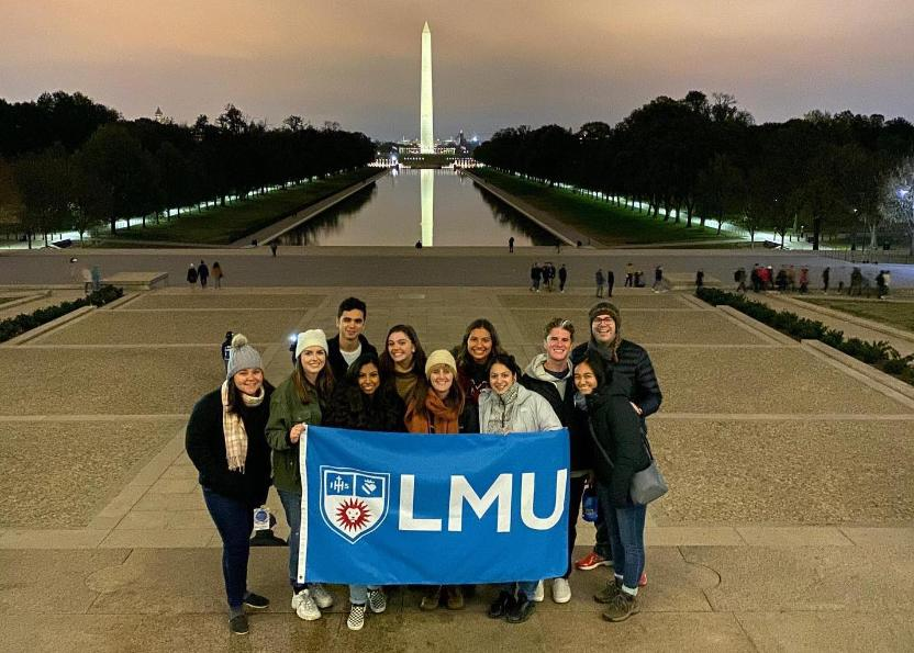 a group of students holding the LMU flag in front of the Washington monument