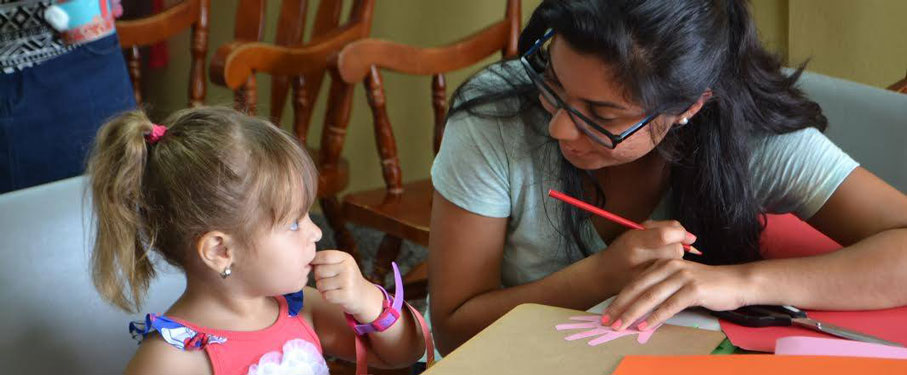 An LMU student working on an art project with a young girl.