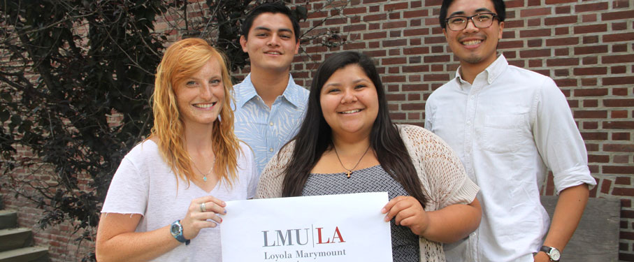 A picture of post-grad volunteers holding an LMU sign