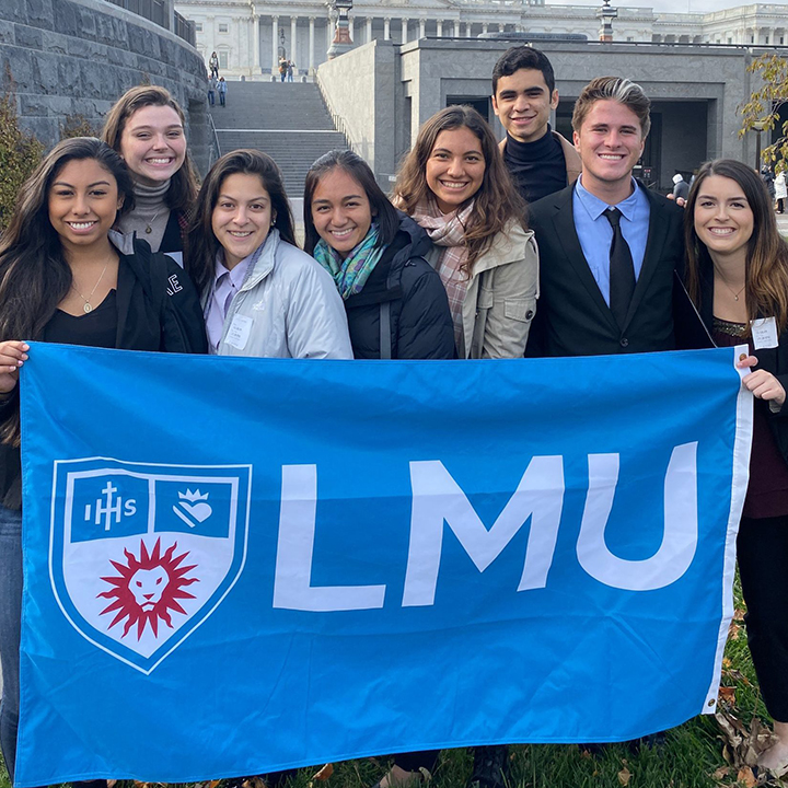 Student standing outside of the nation's capitol building holding an LMU flag