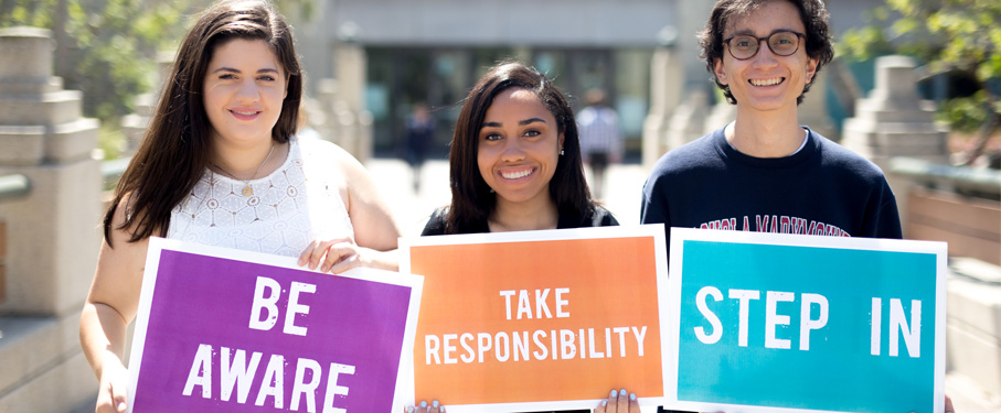 Three students holding signs promoting bystander intervention.