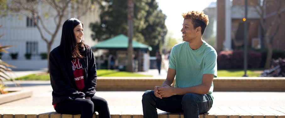 Two students sitting outside at a table having a discussion.