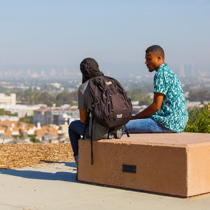 Two students sitting on a bench overlooking the Bluff.
