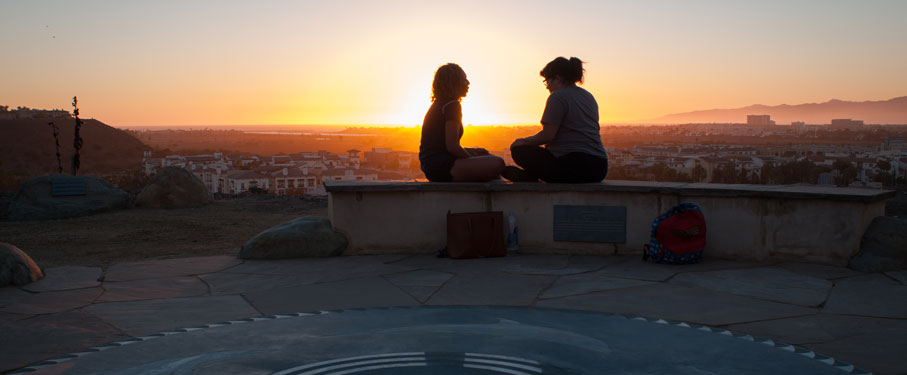 Two students sitting on a bench overlooking the Bluff in front of the sunset