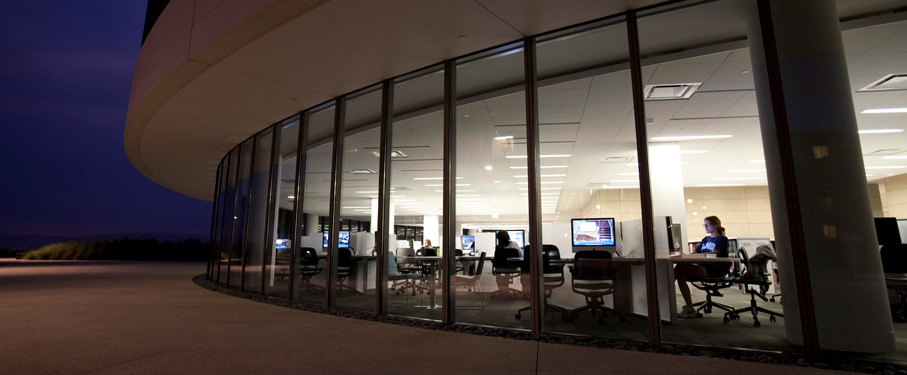 A night-time view looking into the library with students studying at the computers.