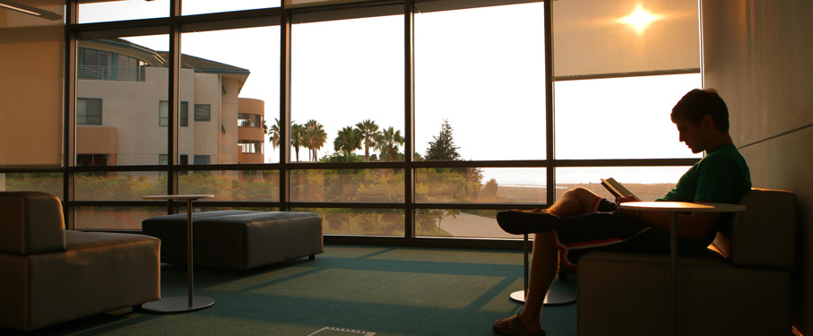 A student reading a book in the library with a view overlooking the bluff.