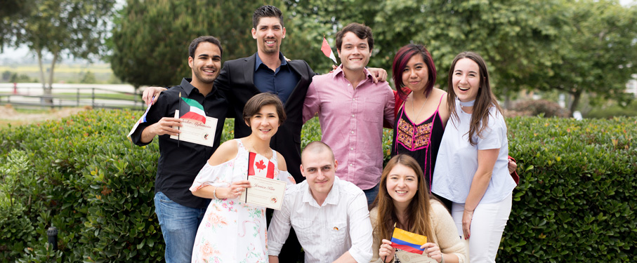 Visiting scholars, some holding up their home country's flag