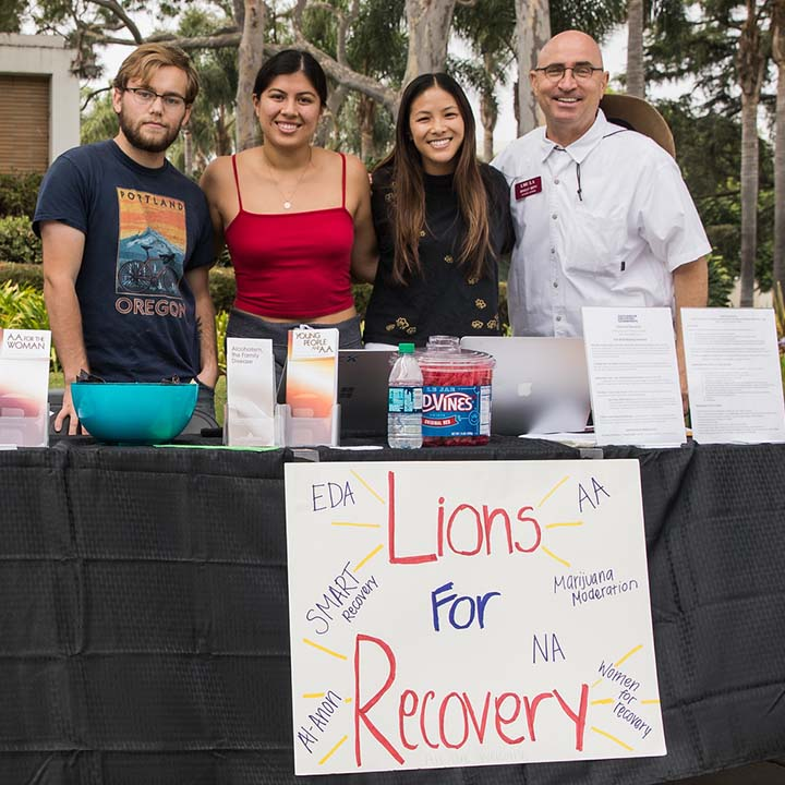 Students standing at table promoting Lions for Recovery