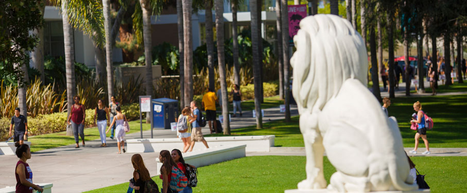 Students walking on campus around the LMU Lion Statue