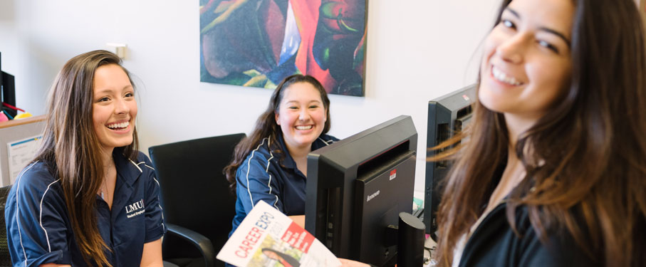 three students in an office smiling into the camera