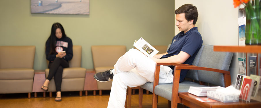 lmu shs student health services male student in shs waiting room reading informational brochure