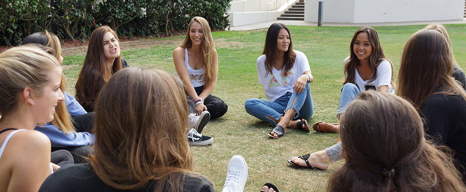 A group of Greek Life students sitting in a circle outside while having a conversation