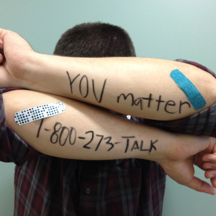 You Matter- National Suicide Hotline (800) 273-TALK writing on a man's arm