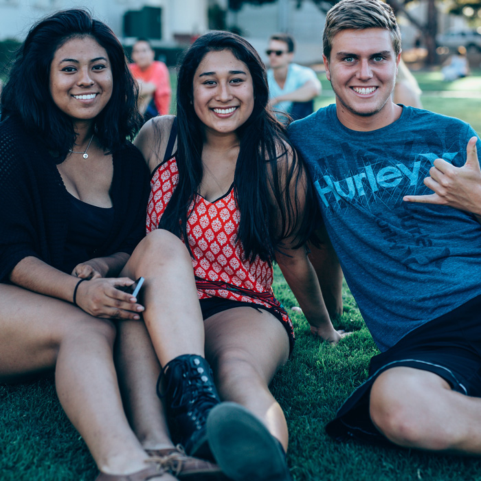 Three LMU students sit on the grass.