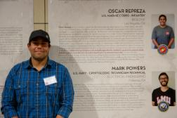 Student smiling for a picture in front of his bio at the Veteran's Exhibit in the library