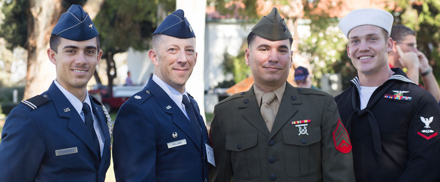Four LMU veterans stand together in uniform.