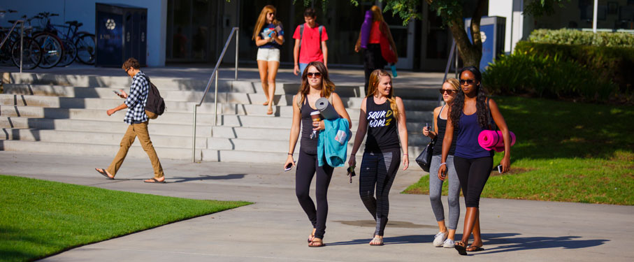 lmu students affairs health wellness four female students walking together in front of Von Der Ahe all holding yoga mats