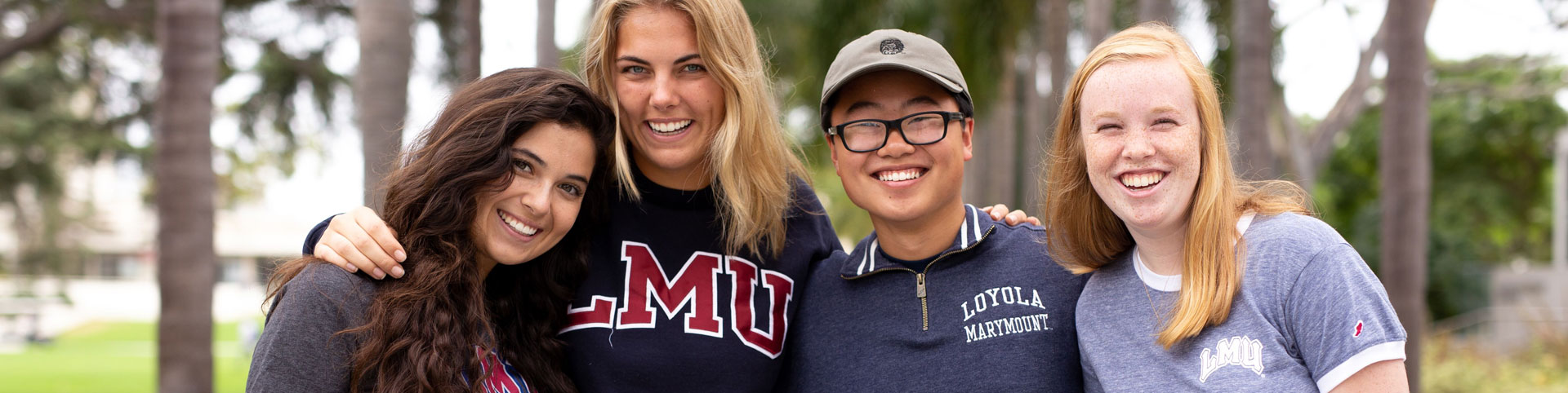 Four students standing together and smiling on Palm Walk